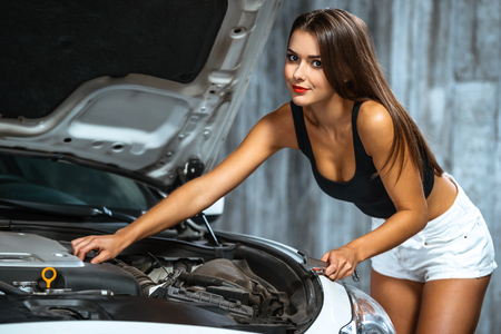 nude girl young: Photo of young female car repair worker. Glamour sexy brunette wearing jean shorts. Girl with wrench looking at camera and working under car cowl