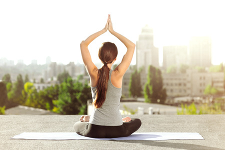 Young woman doing yoga on the mat on the roof, she sitting in lotus posture and looking at city