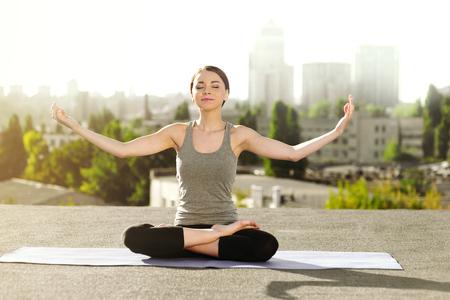Giovane donna che fa yoga sul tappeto sul tetto, seduto nella posizione del loto e meditando Archivio Fotografico - 47714690
