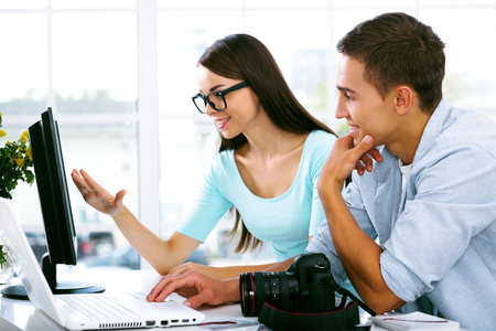 casual business man: Professional photographers with camera and laptop computer working in office, they looking at monitor and smiling