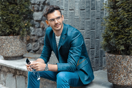 young style: Portrait of stylish handsome young man with bristle standing outdoors. Man wearing jacket and watch. Man with glasses using mobile phone