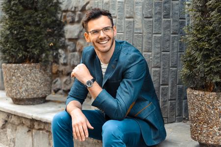 Portrait des stilvollen schönen jungen Mann mit Borste im Freien stehen. Man trägt Jacke und die Uhr. Mann mit Brille fröhlich lächelnd Lizenzfreie Bilder