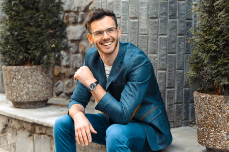 casual attire: Portrait of stylish handsome young man with bristle standing outdoors. Man wearing jacket and watch. Man with glasses cheerfully smiling