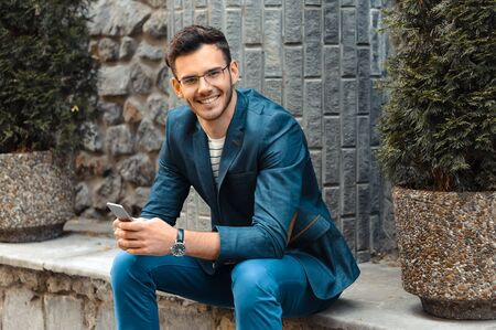 bristle: Portrait of stylish handsome young man with bristle standing outdoors. Man wearing jacket and watch. Man with glasses cheerfully smiling and using mobile phone Stock Photo