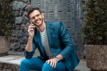 young adult men: Portrait of stylish handsome young man with bristle standing outdoors. Man wearing jacket and watch. Man with glasses cheerfully smiling and using mobile phone Stock Photo