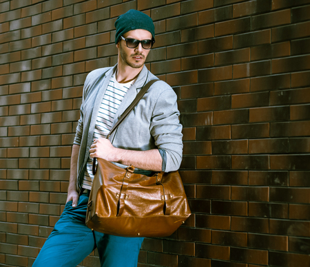 bristle: Portrait of stylish handsome young man with bristle standing outdoors and leaning on brick wall. Man wearing jacket and hat. Man with sunglasses holding leather bag