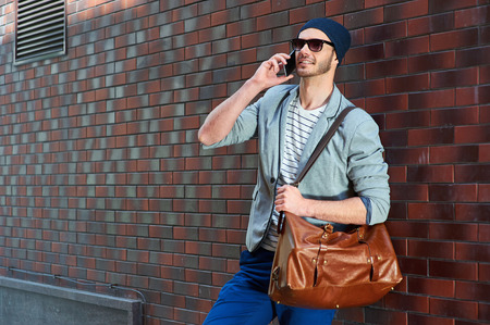 cool man: Portrait of stylish handsome young man with bristle standing outdoors and leaning on brick wall. Man wearing jacket and hat. Man with sunglasses holding leather bag and using mobile phone