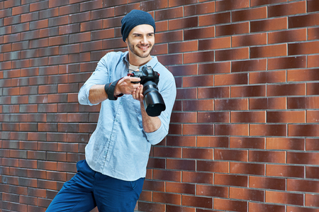 Portrait of stylish handsome young photographer with bristle standing outdoors and leaning on brick wall. Young man wearing shirt and hat. Man with professional camera