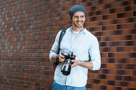 bristle: Portrait of stylish handsome young photographer with bristle standing outdoors and leaning on brick wall. Young man wearing shirt and hat. Man with professional camera