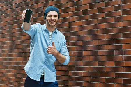 bristle: Portrait of stylish handsome young man with bristle standing outdoors near brick wall. Young man wearing shirt and hat. Man showing mobile phone and thumb up Stock Photo