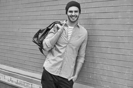 bristle: Portrait of stylish handsome young man with bristle standing outdoors and leaning on brick wall. Young man wearing shirt and hat. Man holding leather bag. Black and white photo