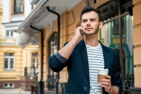 uomini belli: Ritratto del giovane alla moda bello con setole in piedi all'aperto. L'uomo che indossa giacca e camicia. Giovane che parla al telefono cellulare e tenendo la tazza di caffè