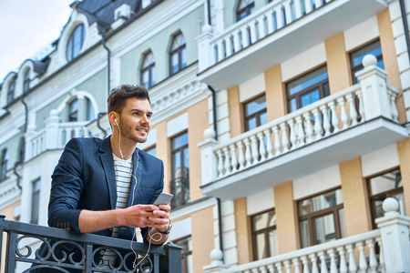 handsome: Portrait of stylish handsome young man with bristle standing outdoors. Man wearing jacket and shirt. Smiling man listening to music with mobile phone and leaning on parapet