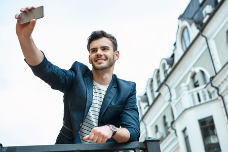 Portrait of stylish handsome young man with bristle standing outdoors. Man wearing jacket and shirt. Smiling man making selfie with mobile phone and leaning on parapet Standard-Bild