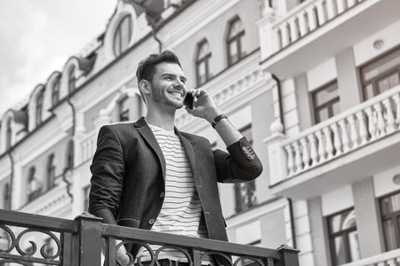 bristle: Portrait of stylish handsome young man with bristle standing outdoors. Man wearing jacket and shirt. Smiling man using mobile phone. Black and white photo