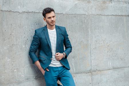 Portrait des stilvollen schönen jungen Mann mit Borste im Freien und stützte sich auf Wand. Man trägt Jacke und Hemd