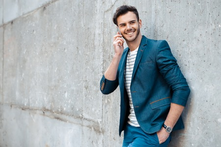 stylish: Portrait of stylish handsome young man with bristle standing outdoors and leaning on wall. Man wearing jacket and shirt. Smiling man using mobile phone Stock Photo