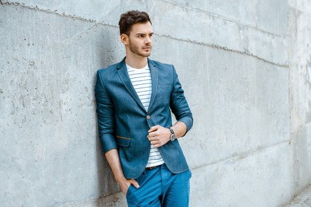 Portrait of stylish handsome young man with bristle standing outdoors and leaning on wall. Man wearing jacket and shirt