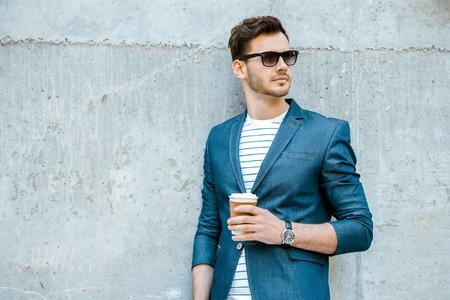 sonnenbrille: Portrait des stilvollen schönen jungen Mann mit Borste im Freien und stützte sich auf Wand. Man trägt Jacke, Sonnenbrille, Hemd und hält Tasse Kaffee