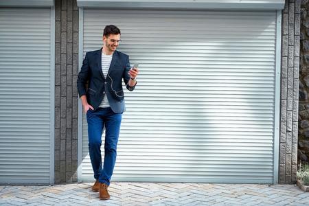 屋外で立って毛とスタイリッシュなハンサムな若い男の肖像画。ジャケットとシャツを着た男。笑みを浮かべて男が携帯電話で音楽を聴く 写真素材