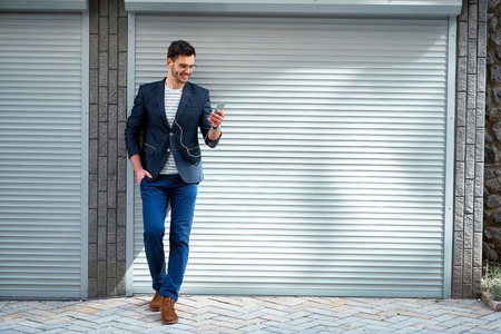 강모 야외 서 세련된 잘 생긴 젊은 남자의 초상화. 재킷과 셔츠를 착용하는 사람 (남자). 휴대 전화로 음악을 듣고 웃는 남자