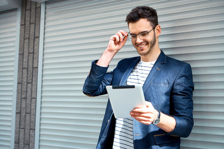 Portrait of stylish handsome young man with bristle standing outdoors. Man wearing jacket, glasses and shirt. Smiling man using tablet computer