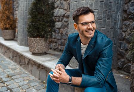 Portret van stijlvolle knappe jonge man met haren zittend op verschansing buitenshuis. Man met jasje en overhemd