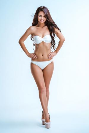 junge nackte m�dchen: Glamour Bild der sch�nen schlanken jungen Frau mit langen lockigen Haaren auf wei�em Hintergrund. M�dchen tragen wei�en Badeanzug und High Heels Schuhe. Brunette Blick in die Kamera und l�chelnd Lizenzfreie Bilder