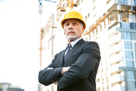 contractor: Business portrait of contractor and developer. Aged businessman with helmet standing near his new construction Stock Photo