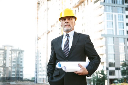 Business portrait of contractor and developer. Aged businessman with helmet standing near his new construction and holding blueprints Standard-Bild