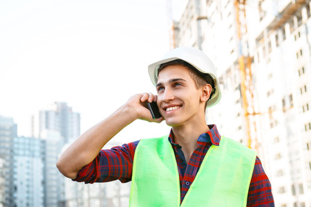 mobile phone: Portrait of builder in uniform. Young man with helmet standing near new unfinished construction and talking on mobile phone Stock Photo