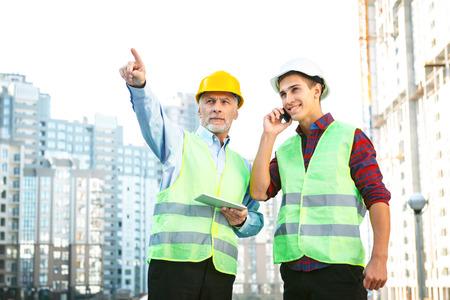 alba�il: Retrato de contratista y constructor en uniformes. Los hombres con cascos de pie cerca de nueva construcci�n sin terminar y con tablet PC con el tel�fono m�vil