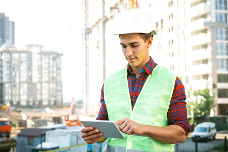 Portrait of builder in uniform. Young man with helmet standing near new unfinished construction and using tablet computer Imagens