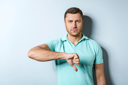 hair problem: Studio shot of handsome young man on grey background. Man wearing polo and showing thumb down
