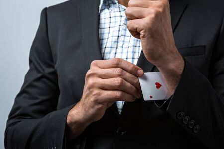 sleeve: Studio shot of young mans hand on grey background. Man wearing jacket and shirt. Man holding card in sleeve