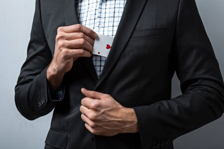 man holding card: Studio shot of young mans hand on grey background. Man wearing jacket and shirt. Man holding card in pocket Stock Photo