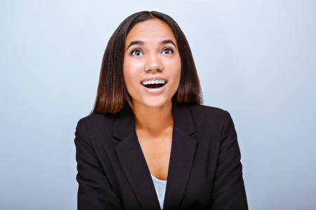 Portrait of beautiful mixed-race young woman standing on grey background. Business woman wearing suit, smiling and wonderingly looking up