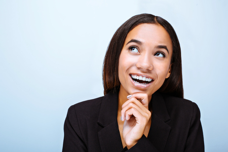 Portrait of beautiful mixed-race young woman standing on grey background. Business woman wearing suit, cheerfully smiling and looking aside