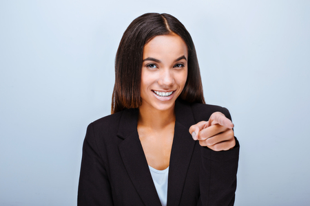 Portrait of beautiful mixed-race young woman standing on grey background. Business woman wearing suit, smiling, looking and pointing at camera