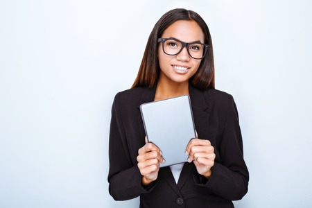 Portrait of beautiful mixed-race young woman standing on white background. Business woman wearing suit and glasses. Woman holding tablet computer and looking at camera