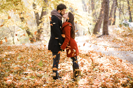 Romantic photo of cute couple outdoors in fall. Young man and woman kissing in falling leaves