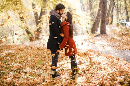 Romantisches Foto des niedlichen Paares draußen im Herbst. Junger Mann und Frau, die in fallenden Blättern küssen
