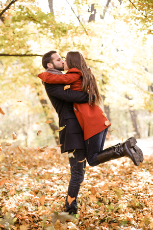 Romantic photo of cute couple outdoors in fall. Young man and woman hugging and kissing