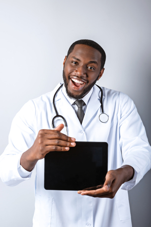 Portrait of male afro american doctor with stethoscope and lab coat. Young doctor smiling and showing tablet computer. Man standing on grey background