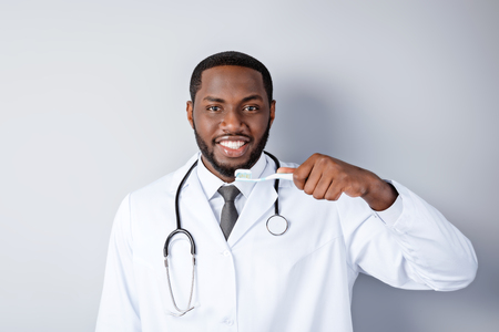 Portrait of male afro american doctor with stethoscope and lab coat. Young doctor smiling, using toothbrush and looking at camera. Man standing on grey background Stock Photo