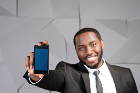 Portrait of handsome afro american businessman. Young stylish businessman showing mobile phone and smiling. Man wearing suit and tie