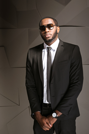 Portrait of handsome afro american businessman. Young stylish businessman wearing suit, tie and sunglasses. Man looking like security guard Stock Photo