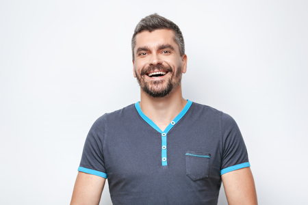 grey haired: Portrait of handsome caucasian man with grey beard standing on white background. Man looking at camera and smiling Stock Photo