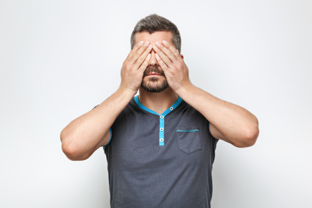 Portrait of handsome caucasian man with grey beard standing on white background. Man covering his eyes with hands Standard-Bild