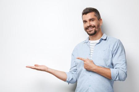 Portrait de bel homme élégant caucasien avec barbe grise debout sur fond blanc. Homme pointant sur un mur blanc vide Banque d'images